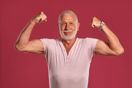 Handsome mature man posing against a pink studio background.