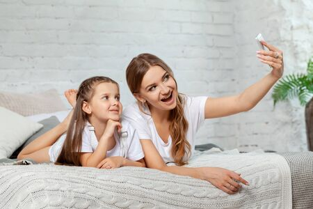 Indoor portrait of a beautiful mother with her charming little daughter posing against bedroom interior.