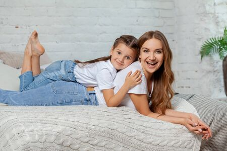 Indoor portrait of a beautiful mother with her charming little daughter posing against bedroom interior. Banco de Imagens - 128585965