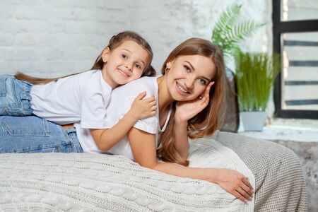 Indoor portrait of a beautiful mother with her charming little daughter posing against bedroom interior. Banco de Imagens - 128585972