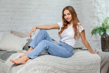 Indoor portrait of a beautiful blonde woman posing sitting on a bed.