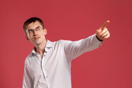 Young man in a classic white shirt is posing over a pink background.