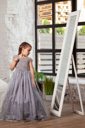 Indoor portrait of a little charming girl wearing in a beautiful dress. Stock Photo