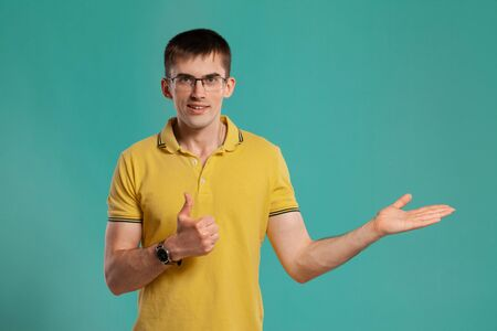 Handsome guy in a yellow casual t-shirt is posing over a blue background. 写真素材