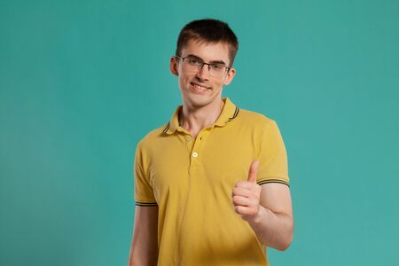 Handsome guy in a yellow casual t-shirt is posing over a blue background. Banque d'images