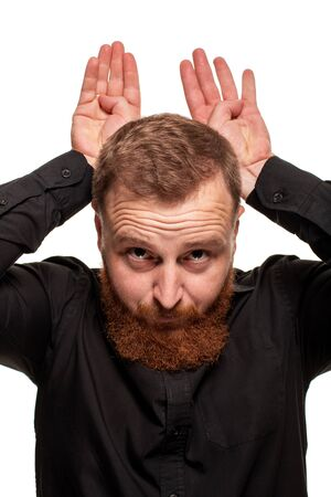 Portrait of a young, chubby, redheaded man in a black shirt making faces at the camera, isolated on a white background