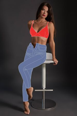 Full-length portrait of an attractive woman in fashionable cartoon jeans and sensual lingerie posing sitting on a bar chair.