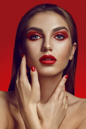 Close-up glamour portrait of a beautiful half-naked model with bright make-up posing over a red background. Stock fotó