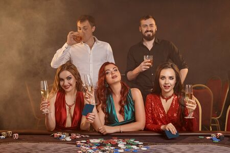 Group of a young wealthy friends are playing poker at a casino. Stok Fotoğraf