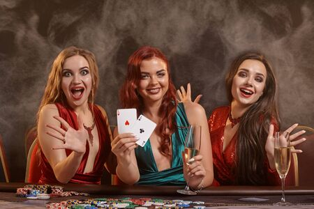 Group of a young wealthy ladies are playing poker at a casino.