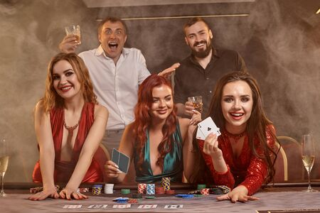 Group of a young wealthy friends are playing poker at a casino. Imagens