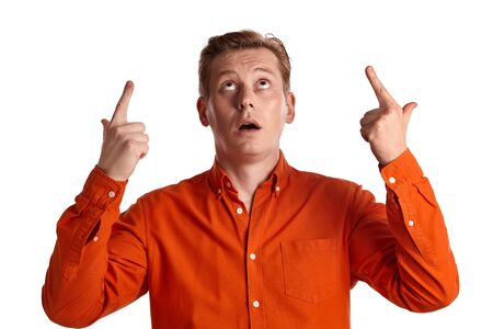 Close-up portrait of a ginger guy in orange shirt posing isolated on white background. Sincere emotions. Banque d'images