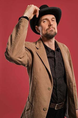 Middle-aged man with beard and mustache, wears black hat and brown jacket posing against a red background. Sincere emotions concept.