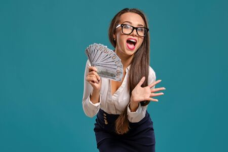 Brunette girl in glasses, wearing in a black short skirt and white blouse is posing holding a fan of hundred dollar bills against a blue background. 版權商用圖片