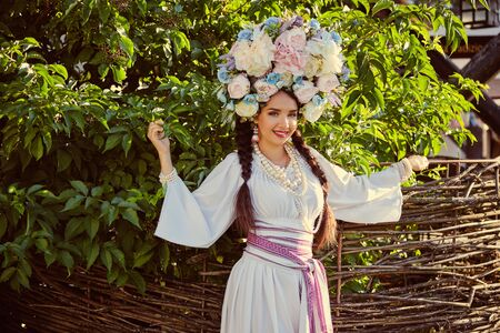 Brunette girl in a white ukrainian authentic national costume and a wreath of flowers is posing against a wooden wicker fence. Stock fotó