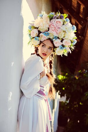 Brunette girl in a white ukrainian authentic national costume and a wreath of flowers is posing against a white hut.