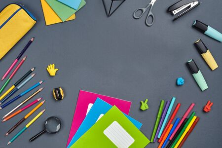 Flat lay photo of workspace desk with school accessories or office supplies on gray background. Stockfoto