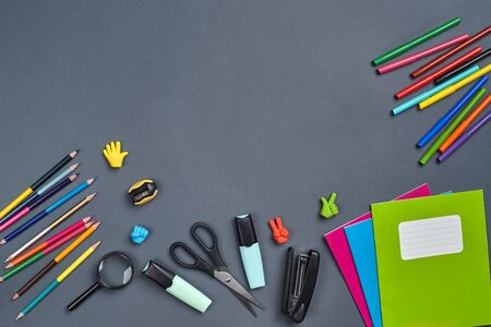 Flat lay photo of workspace desk with school accessories or office supplies on gray background. 免版税图像