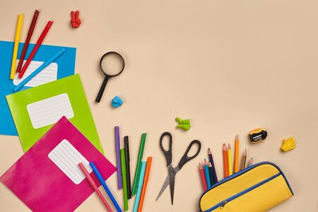 Flat lay photo of workspace desk with school accessories or office supplies on pink background.