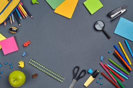 Flat lay photo of a workspace desk with school accessories, such as felt-tip pens, marker, yellow pencil case, erasers, buttons, paper clips, scissors, magnifier, pencils, stapler, pencil sharpener, green apple, ruler and stickers. Mockup of learning process. Top view with copy space on gray background. Stockfoto