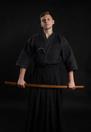 Kendo guru wearing in a traditional japanese kimono is practicing martial art with the shinai bamboo sword against a black studio background. Stok Fotoğraf - 129255165