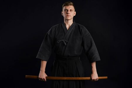 Kendo guru wearing in a traditional japanese kimono is practicing martial art with the shinai bamboo sword against a black studio background.