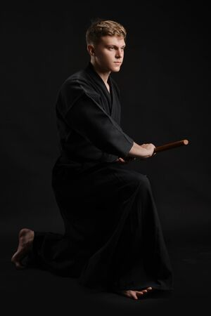Kendo guru wearing in a traditional japanese kimono is practicing martial art with the shinai bamboo sword against a black studio background. Stok Fotoğraf - 129255171