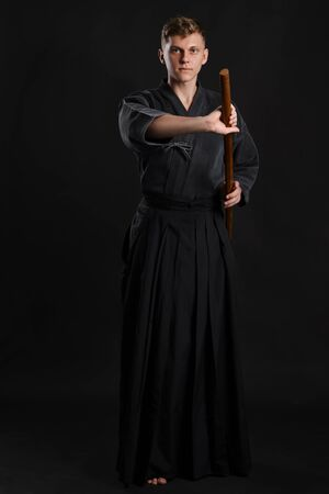 Kendo guru wearing in a traditional japanese kimono is practicing martial art with the shinai bamboo sword against a black studio background. Stok Fotoğraf - 129255093