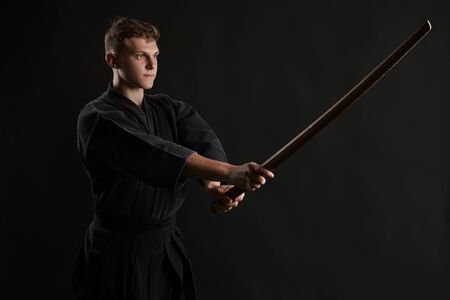 Kendo guru wearing in a traditional japanese kimono is practicing martial art with the shinai bamboo sword against a black studio background. Stok Fotoğraf - 129255116