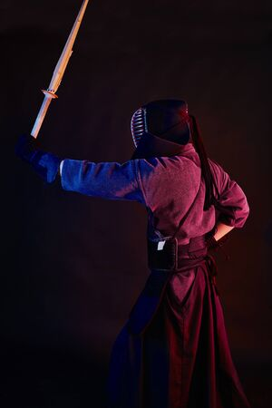 Close up shot, Kendo fighter wearing in an armor, traditional kimono, helmet practicing martial art with shinai bamboo sword, black background.