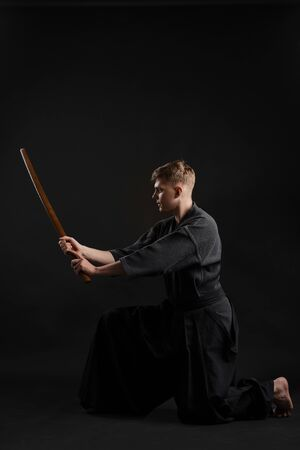 Kendo guru wearing in a traditional japanese kimono is practicing martial art with the shinai bamboo sword against a black studio background. Stok Fotoğraf - 129254951