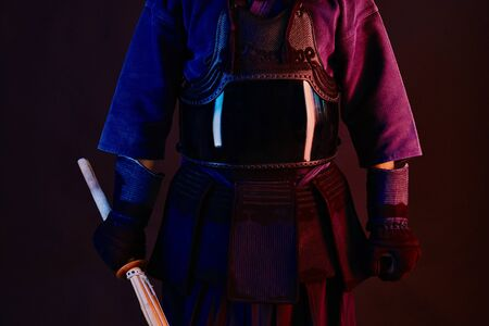 Close up shot, Kendo fighter wearing in an armor, traditional kimono is practicing martial art with shinai bamboo sword, black background.