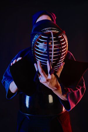 Courage Kendo instructor wearing in an armor and traditional kimono is tying the lacing on his helmet standing against a black studio background. Combat training, sportsmanship, close up.