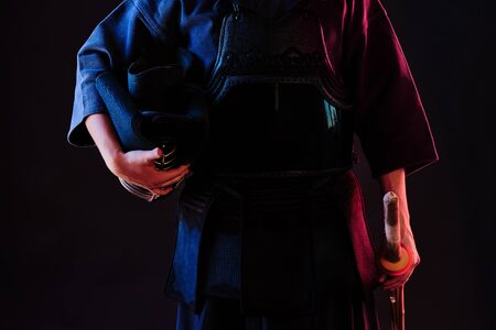 Good-looking Kendo master wearing in an armor and traditional kimono is holding his helmet and shinai bamboo sword while posing against a black studio background. Combat training, sportsmanship, close up. Stock Photo