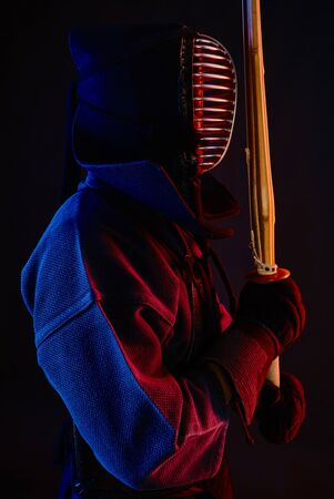 Muscular Kendo warrior wearing in an armor, traditional kimono and helmet is practicing martial art with the shinai bamboo sword posing sideways against a black studio background. Combat training, sportsmanship, close up.
