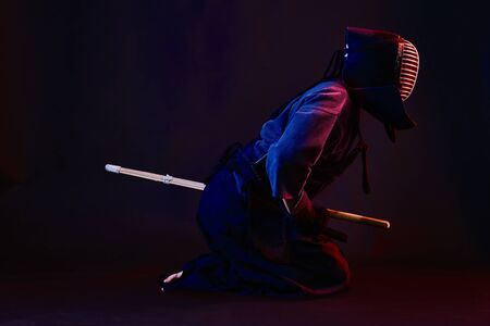 Robust Kendo master wearing in an armor, traditional kimono and helmet is practicing martial art with the shinai bamboo sword posing sitting sideways against a black studio background. Combat training, sportsmanship, close up. Full length, barefoot.