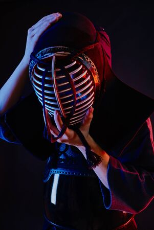 Close up shot, Kendo fighter wearing in an armor and traditional kimono is tying the lacing on his helmet standing against a black background.