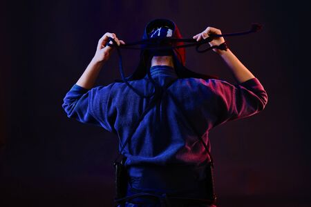 Close up shot, Kendo fighter wearing in an armor and traditional kimono is tying the lacing on his helmet standing back against a black background.
