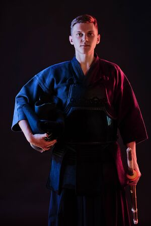 Kendo fighter wearing in an armor, traditional kimono is holding his helmet and shinai bamboo sword while posing on a black background. Close up. Zdjęcie Seryjne