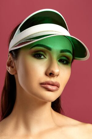 Close up portrait of a brunette nude model girl in a green visor, with professional evening make-up, posing against a pink background. Stockfoto