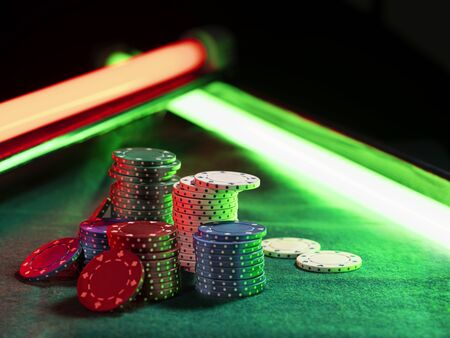 Close-up shot of a multicolored chips piles, some of them laying nearby on green cover of playing table, under green and red neon lights. Black background. Close-up Imagens