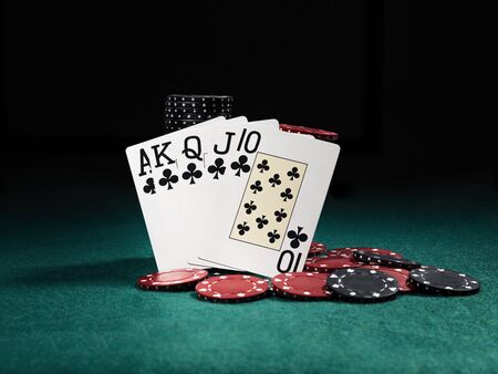 Close-up photo of the winning combination in poker standing leaning on high quality chips piles, some of them are laying nearby on a green cover of a playing table, against black background. Gambling entertainment, playing cards, casino concept. Stock Photo