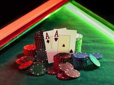 Close-up shot of two aces hearts and diamonds standing leaning on multicolored chips piles, some of them are laying nearby on a green cover of a playing table, against black background, under green and red neon lights. Gambling entertainment, playing cards, poker, casino concept.