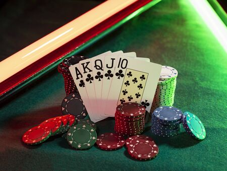 Close-up shot of the winning combination in poker standing leaning on colored chips piles, some of them are laying nearby on a green cover of a playing table, against black background, under green and red neon lights. Gambling entertainment, playing cards, casino concept. Stock Photo