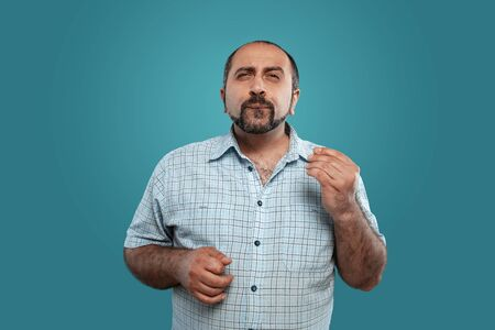 Close-up portrait of a brunet middle-aged man with beard, dressed in a light checkered shirt and posing against a blue background. 写真素材