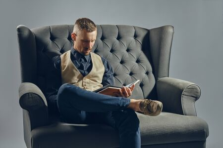 Man with stylish mustache, dressed in black shirt and trousers, beige vest is sitting on dark sofa, reading a magazine. Grey background, close-up.