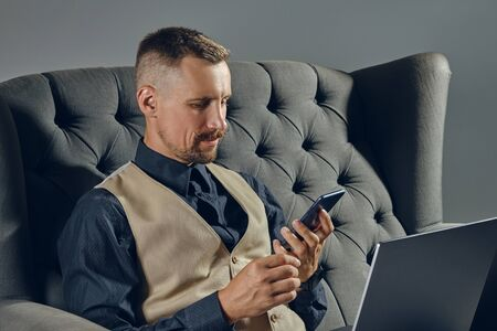Man with stylish mustache, dressed in black shirt and beige vest is sitting on dark sofa, using his laptop and smartphone. Grey background, close-up.