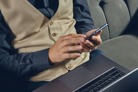 Hands of a man, dressed in black shirt and beige vest is sitting on dark sofa, using his laptop and smartphone. Grey background, close-up.