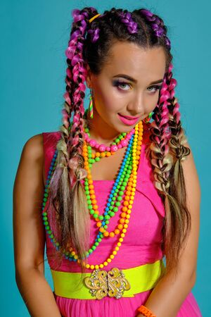 Lovely girl with a multi-colored braids hairstyle and bright make-up, posing in studio against a blue background.