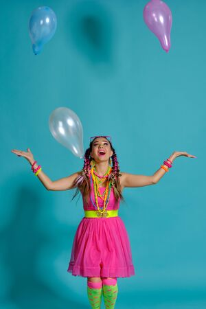 Lovely girl with a multi-colored braids hairstyle and bright make-up, posing in studio with air balloons against a blue background.